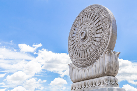 Carved sandstone Dharmachakra on blue sky background