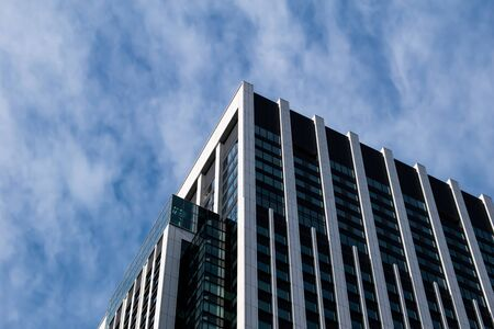 Top corner of office building a blue sky and cloud somewhere in Ueno, Japan gives a modern feel. Taken with the face upward angle. Фото со стока