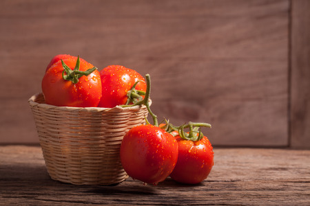 juicy red tomatoes in basket on wooden table Stockfoto