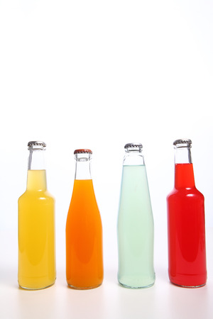 juice glass: Drinks in glass bottles isolated on white