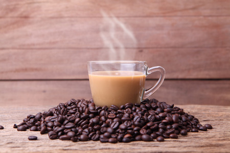 coffeetree: Cup of black coffee and coffee beans on wooden . Stock Photo