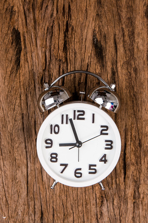 white alarm clock on wooden old background