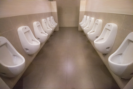 row white urinals in mens bathroom toilet Stock Photo
