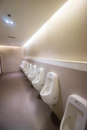 latrine: row white urinals in mens bathroom toilet Stock Photo