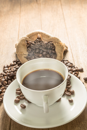 White coffee cup and coffee beans on wood background. Stock Photo