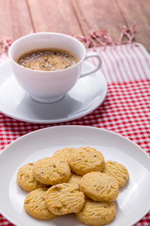 cookies on white plate and cup of coffee