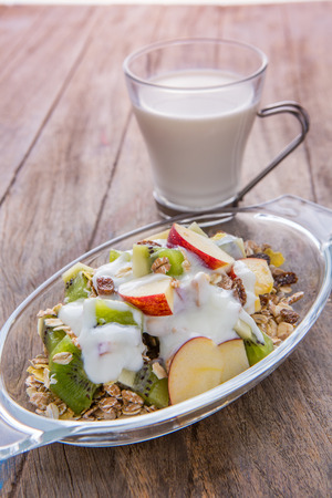 Healthy bowl of muesli, apple, fruit, nuts and milk for a nutritious breakfast