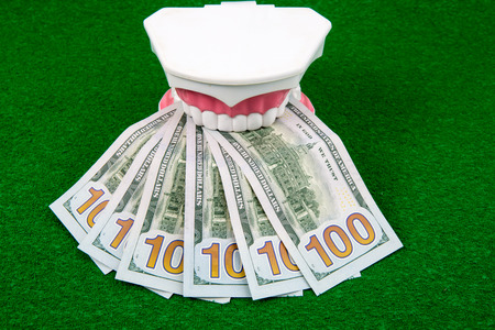 surgery expenses: tooth model and dollar money on green background Stock Photo