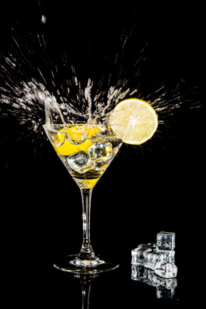alcoholic drink: cocktail with splash and  lime isolated on black