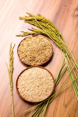 arroz: arroz con cáscara y marrón en el plato y arroz planta de madera