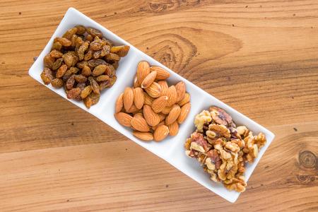 worktop: Mixed delicacies, walnut, currant, almond on wooden worktop