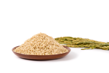 plantation: brown rice on wooden plateand paddy on white background