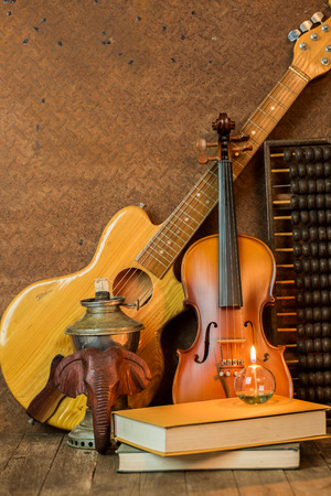fiddles: Acoustic guitar,violin,book and abacus lay on floor and steel background interior decoration still life style Stock Photo