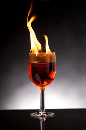 wine glass with burning alcohol on black background