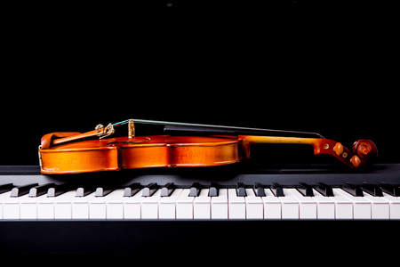 Violin on the piano on a black background 版權商用圖片