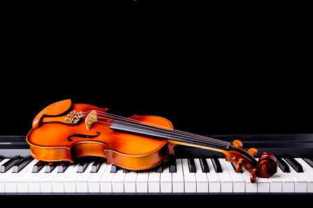 violines: Violín en el piano sobre un fondo negro Foto de archivo