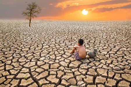Kind zit op gebarsten aarde De oude man zit op gebarsten aarde in het droge gebied