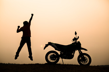winner man: Silhouette of man jumping on the background of motorcycle and sunset