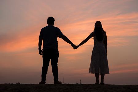 Silhouette di coppia per mano al tramonto