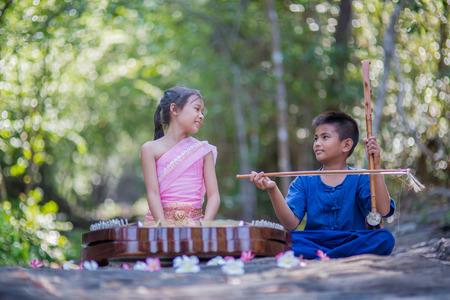 fiddles: Thai girl in Thai dress playing Thai music inthe park Stock Photo