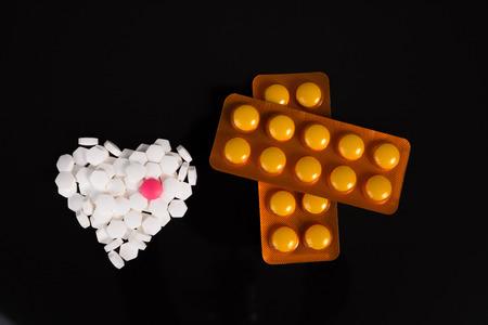 forme: blanc en forme de coeur de la drogue sur fond noir Banque d'images