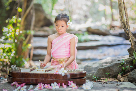 Thai girl in Thai dress playing Thai music inthe park Stock Photo