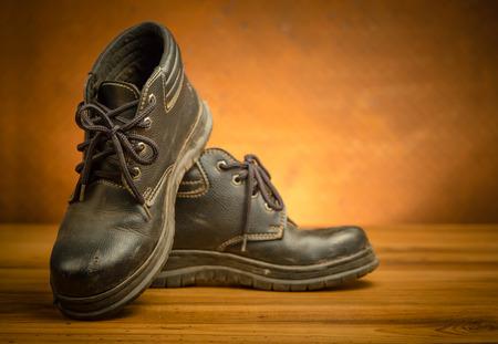 zapatos de seguridad: zapatos de seguridad de color negro en el suelo de madera con el espacio de la copia