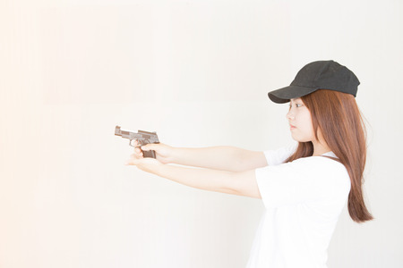 youth crime: Young asian Woman holding the gun
