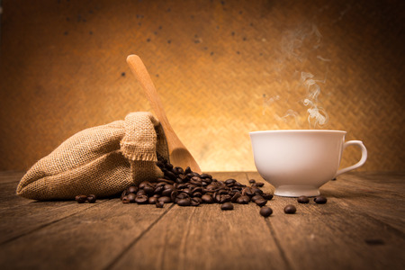 Cup of coffee and coffee beans on sackcloth on wooden with old steel background