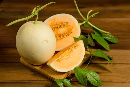 Cantaloupe: Yellow cantaloupe melon on the wooden background.