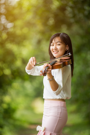 asia woman playing violin in garden with sunshine