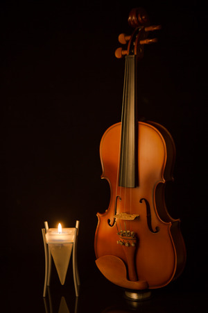 violins: classical violins with  candle on black background Stock Photo
