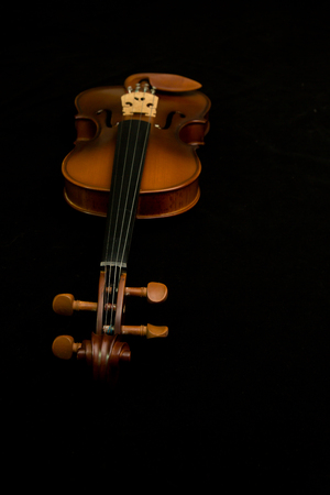 violins: classical violins lying on black background Stock Photo