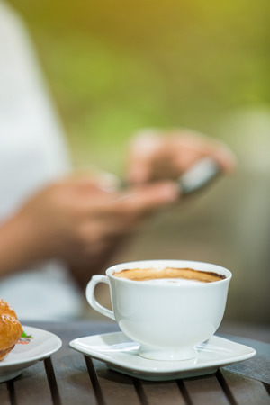woman drinking coffee and usr smartphone in the garden