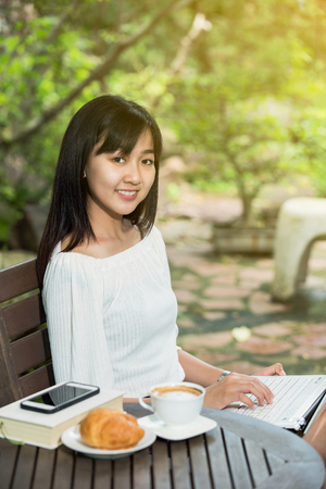 japanes: asian woman drink coffee and reading book in garden Stock Photo