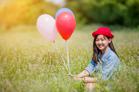 Asian girl with balloons plays in a field with sunshine