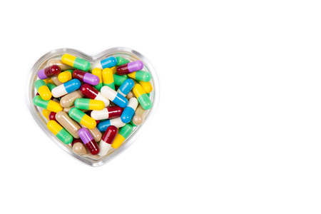 pills in the shape of  heart isolated on white