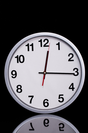 standard steel: black and white chrome clock on black reflective Stock Photo