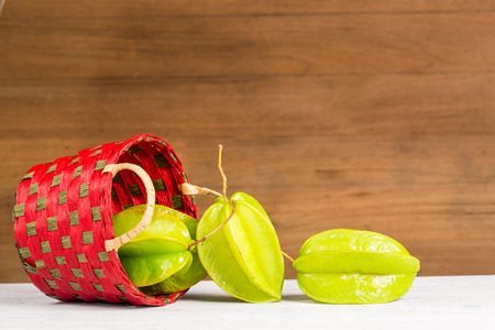 star fruit in the basket, on wooden background Stock Photo