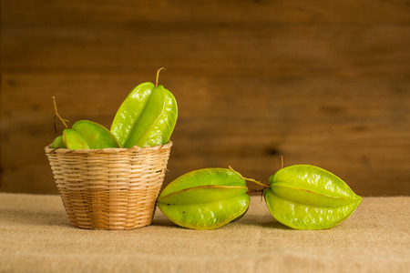 unripened: star fruit in the basket, on wooden background Stock Photo