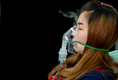 woman holds mask inhaler  treatment of asthma. breathing through a steam nebulizer 版權商用圖片