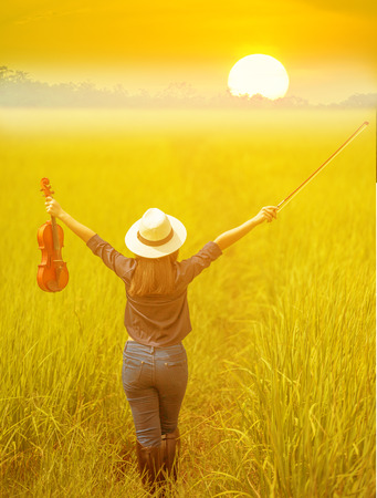 Young woman holding violin on rice field with sunset background