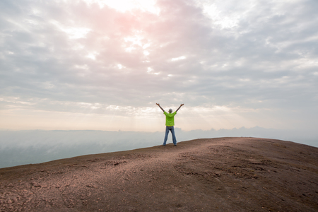 Man with arms outstretched in mountains