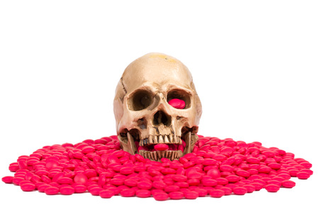 skull hold drugs red pill in the mount with white background