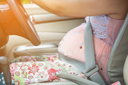 Pregnant woman wear safety belt in the car