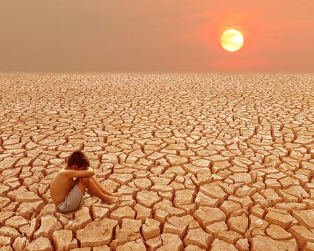 Enfant assis sur terre craquelée dans la zone aride Banque d'images - 65741423