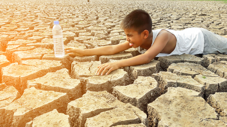 thirst: Child lying on cracked earth in the arid area