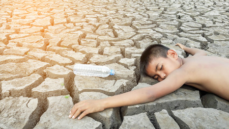 metaphoric: Child lying on cracked earth in the arid area