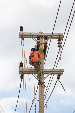 power wrench: Electrician lineman repairman worker at climbing work on electric post power pole