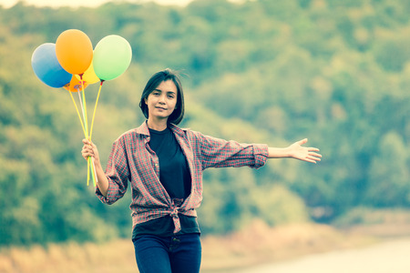 Happy young woman holding balloon in background nature,hipster style